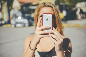blond woman holding a phone taking a photo